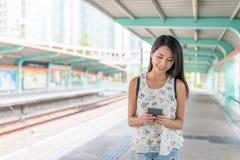 Женщина используя мобильный телефон и идущ на платформу стоковое фото rf