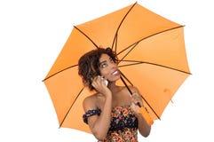 Женщина используя мобильный телефон под зонтиком стоковые изображения