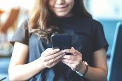 Женщина используя мобильный телефон пока сидящ в аэропорте стоковое фото