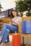Женщина используя мобильный телефон после больших покупок в торговом центре стоковые фото