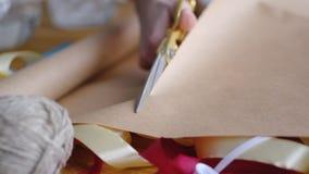 Женщина, используя ножницы, режет бумагу для того чтобы обернуть подарок на свадьба, день рождения, рождество, пасха или другой п стоковые изображения