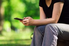 Женщина используя парк smartphone публично стоковые фотографии rf
