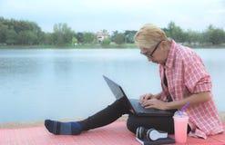 Женщина используя портативный компьютер пока сидящ около реки стоковое изображение rf