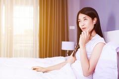 Женщина используя прибор наушника на мобильном телефоне на кровати в спальне Стоковые Изображения RF