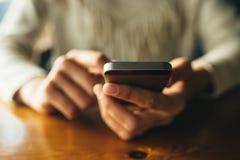 Женщина используя смартфон на деревянном столе в кафе стоковые изображения rf