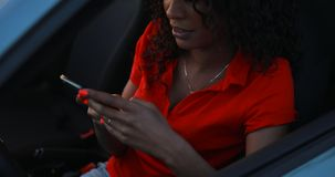 Женщина используя смартфон сидя в автомобиле, отправляет сообщение сток-видео