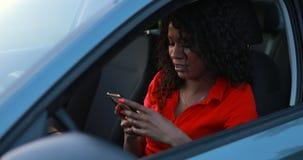 Женщина используя смартфон сидя в автомобиле, отправляет сообщение акции видеоматериалы
