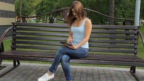 Женщина используя таблетку в парке города женщина сидя на стенде с устройствами в парке акции видеоматериалы