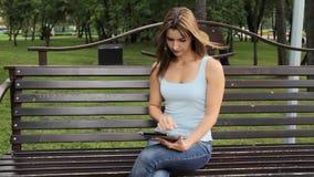 Женщина используя таблетку в парке города женщина сидя на стенде с устройствами в парке видеоматериал