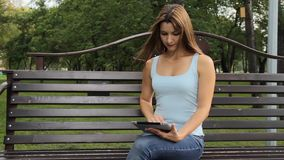 Женщина используя таблетку в парке города женщина сидя на стенде с устройствами в парке сток-видео