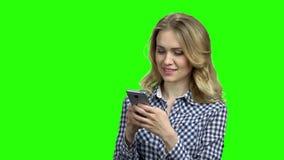 Женщина используя телефон на зеленой предпосылке экрана