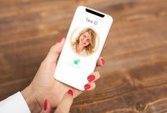 Женщина используя технологию опознавания ` s мобильного телефона лицевую стоковые изображения rf
