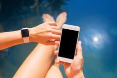 Женщина используя умные цифровые часы и мобильный телефон стоковые фото