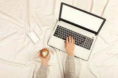Женщина используя умный телефон на ее кровати стоковые фото