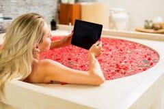 Женщина используя цифровую таблетку в ванне Стоковое Изображение RF