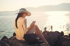 Женщина используя цифровую таблетку на море Стоковые Изображения