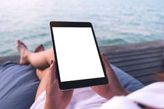Женщина используя черный ПК таблетки с пустым белым экраном настольного компьютера пока сидящ морем Стоковые Фото