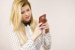 Женщина используя smartphone проверяя социальные средства массовой информации стоковое изображение