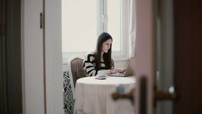 Женщина использует компьтер-книжку и наслаждаться кофе утра на яркий обедать взгляд через открыть двери Стоковое Изображение RF