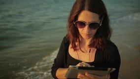 Женщина использует ПК таблетки на взморье видеоматериал