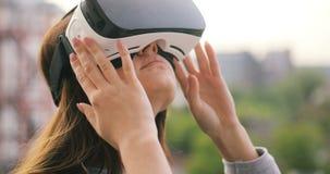 Женщина использует стекла виртуальной реальности на девушки приключения города технологии строительства крыши заходе солнца прибо сток-видео