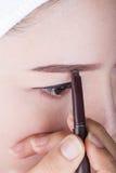 Женщина используя бровь состава карандаша Стоковые Фото