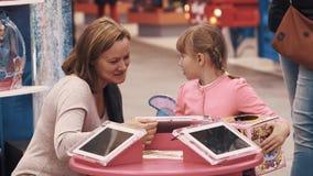 Женщина используя держатель в планшете таблицы с дочерью на торговом центре сток-видео