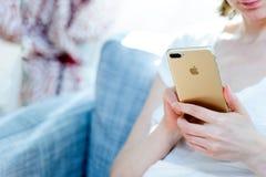 Женщина используя интернет нового smartphone iphone 7 добавочного занимаясь серфингом так Стоковая Фотография