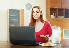 Женщина используя компьтер-книжку во время завтрака Стоковые Фотографии RF