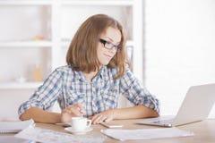 Женщина используя компьтер-книжку и делающ обработку документов Стоковое Изображение