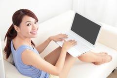 Женщина используя компьтер-книжку на софе