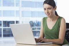 Женщина используя компьтер-книжку на столе офиса Стоковое Изображение RF