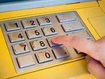 Женщина используя машину ATM для того чтобы разделить деньги Стоковое Изображение