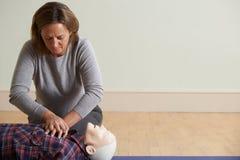 Женщина используя метод CPR на кукле в классе скорой помощи стоковые изображения rf