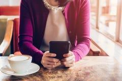 Женщина используя мобильный телефон в кафе Женское усаживание в кафе и чашке Стоковое Изображение