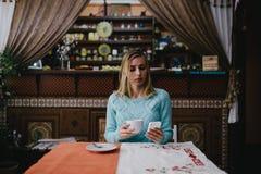 Женщина используя мобильный телефон в кафе Стоковые Изображения RF