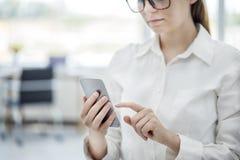 Женщина используя мобильный телефон в офисе Стоковые Фотографии RF