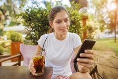 Женщина используя мобильный телефон на парке стоковое изображение