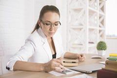 Женщина используя мобильный телефон на таблице Стоковое Изображение RF