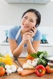 Женщина используя мобильный телефон перед овощами в кухне стоковые изображения