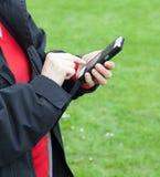 Женщина используя мобильный телефон снаружи Стоковые Изображения RF