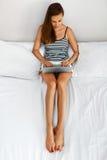 Женщина используя дом компьютера Деятельность девушки, тетрадь компьтер-книжки на кровати Стоковое фото RF