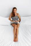 Женщина используя дом компьютера Деятельность девушки, тетрадь компьтер-книжки на кровати Стоковое Изображение