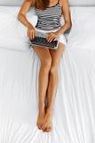 Женщина используя дом компьютера Деятельность девушки, тетрадь компьтер-книжки на кровати Стоковые Изображения