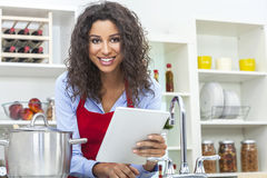 Женщина используя планшет варя в кухне Стоковые Изображения