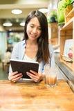 Женщина используя планшет в кафе Стоковое Фото