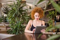 Женщина используя планшет в ресторане Стоковые Изображения