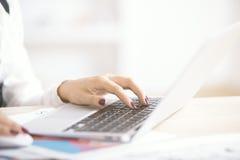Женщина используя сторону компьтер-книжки Стоковое Изображение