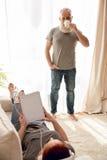Женщина используя таблетку и слушая музыку с кофе человека выпивая Стоковая Фотография