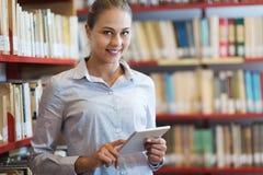 Женщина используя таблетку на библиотеке стоковое изображение